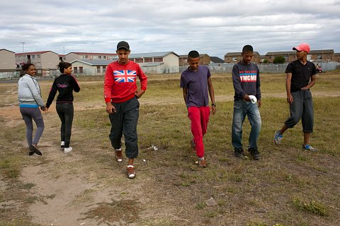 Ashwin Pietersen walks through Manenberg with his friends. Ashwin's sweatshirt bears the symbol of the Hard Livings gang, the main rival of the Americans gang. <br> Manenberg, March 2014.