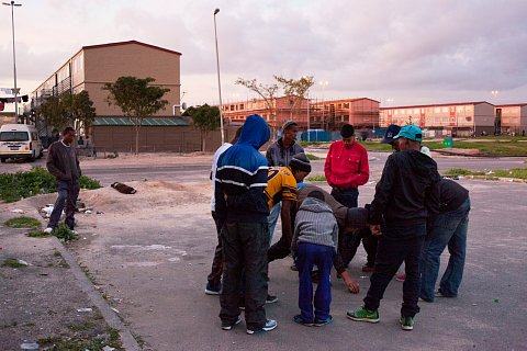 Youth in Manenberg gamble for small coins at dusk. Ashwin Pietersen is pictured picking up a coin in the middle of the group of young men. Edmond, Ashwin's cousin, stands to the left of the group, watching for rival gangs. In late 2014, 20 gang-related murders reportedly took place within two weeks in Manenberg and neighboring Hanover Park.<br> Manenberg, September 2014.
