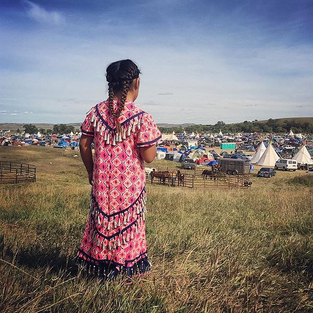 Aeris Davis, 8, looks over Sacred Stone Camp in Cannon Ball, ND. Davis is a member of the Turtle Mountain Band of Chippewa Indians. There are over 5,000 people in the camp and over 250 tribal nations are present. #NoDapl #cannonball #northdakota #usa #cle