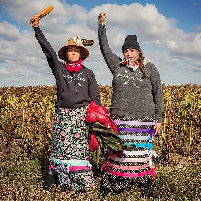"""Women against the construction of the Dakota Access Pipeline stand in a field of sunflowers outside Cannon Ball, N.D. on Sept. 25, 2016. Their shirts say""""protector"""", which sends the message that those gathered in opposition to the pipeline are """"protectors"""
