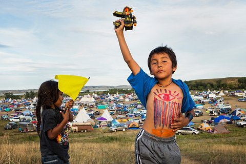 Youth play in the Oceti Sakowin camp on the banks of the Cannonball River in N.D. Since April 2016, thousands of Native and non-Native protesters have joined the Standing Rock Sioux Tribe in their fight against the construction of the Dakota Access Pipeline. If built, the pipeline will be laid under the Missouri River, located on the edges of the Standing Rock Sioux Reservation. The pipeline threatens the availability of clean water and disrupts sacred sites and burial grounds. September 10, 2016.