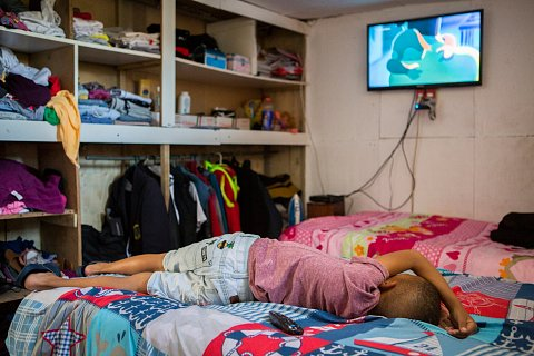 Joshua Adams watches TV inside the room he shares with his two older sisters, Tosha and Tonya.<br>Manenberg, March 2017.