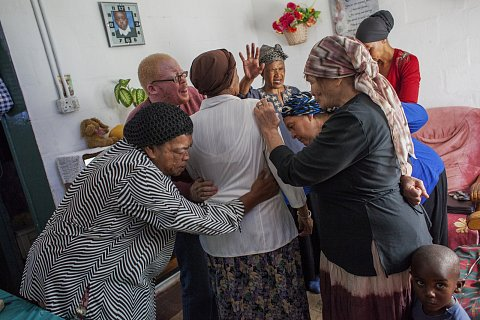 Neighbors gather for a prayer meeting inside Debby Lottering's home. The group prays for each other, their families, and for their community. <br> Manenberg, March 2014.