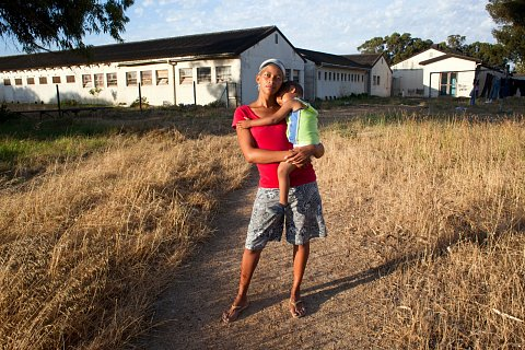 "Naomi Lottering with her son, Shaquille, at the ARK, a center for rehabilitation in Faure, a suburb 15 miles from Manenberg. In her early teens Naomi began spending time on the streets. Today, she doesn't contact her family for weeks or months at a time, but whenever she comes home to Manenberg she is welcomed by her sister, Debby, and father, Franz. ""I've never been homeless, I'm just a drifter,"" says Naomi. <br>Faure, December 2012."