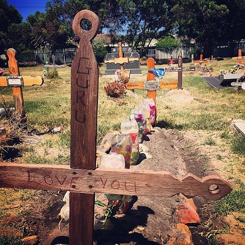 "Ashwin Pietersen was killed in a gang related shooting in 2014. Charmaine, his mother, and his sister, Nella, rearranged the dirt and artificial flowers, wrote Ashwin's nickname, ""Guru,"" and ""Love you"" on the cross, then put rocks around the grave. When they visited Ashwin nearly a month ago for his 22nd birthday, they also put rocks around the grave, but they were stolen or moved to another plot. For Charmaine and Nella to visit the cemetery from Manenberg they must take a train and a taxi, which costs nearly R100, a prohibitive cost. #lovefrommanenberg #manenberg #capetown #capeflats #cemetery #southafrica #plumsted"