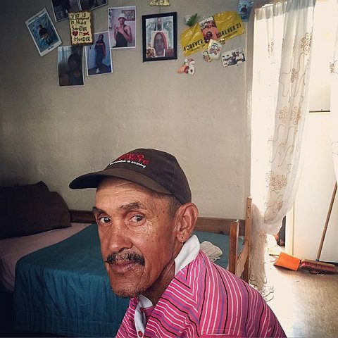 """John Pietersen, 58, has been in Manenberg 30 years. He stays with his younger sister, Charmaine, and several nieces and nephews. """"I don't have friends in Manenberg,"""" he says. """"I worked for the postal service and then was an engineer for 12 years. I'm just waiting for my pension so I can travel."""" John is a member of one of three families I've been following in Manenberg since 2011. He loses his breath walking from the kitchen to the living room, but won't go to go to the clinic. I've never seen him outside the house. He's always ready with a warm welcome when I arrive.  #lovefrommanenberg #manenberg #capetown #capeflats #southafrica #family"""