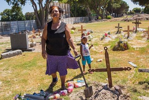 "Charmaine Pietersen visits the cemetery as often as possible, always bringing a shovel to keep the dirt in place on top of her son's grave. Here, her granddaughter, Chelsea, is by her side. On December 21, 2014, Ashwin Pietersen, Charmaine's son, was killed outside their home in Manenberg by a rival gang. Charmaine says, ""The years go on and the months go on. We know he's in a safe place. I don't need to worry where Ashwin is at night if they start shooting or if there is violence in Manenberg. We can sleep peacefully now. I'm glad for Ashwin, for where he is now.""<br> Plumsted, January 2016."