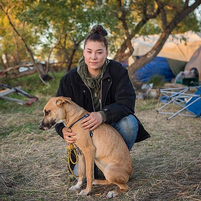 "Adriana Furlong 21, is a member of the Alaskan Aleut Tribe. She lives in Seattle, Wash. and traveled to the Oceti Sakowin camp near Cannon Ball, N.D. to join the #NoDAPLE protests. Here, Furlong sits with a dog she calls ""Mama"" or ""MaeMae,"" who she found"