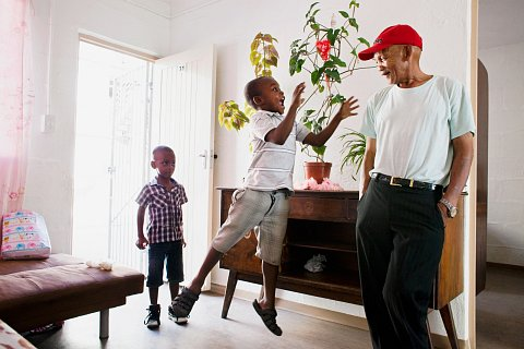 Meezie and Zobie Lottering, Debby's children, play with their Grandpa Franz in the living room of Franz's home, where he lives with his third wife and her children. Franz sees his grandchildren almost daily, taking on childcare duties that allow his daughter, Debby, to work longer hours.<br> Manenberg, March 2014.