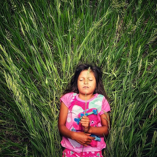 Germaine Grassrope, a girl with an imagination and spark for life that's contagious, plays outside her home in Lower Brule, South Dakota.