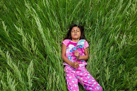 Germaine Grassrope plays in the grass outside her home. <br>Lower Brule, South Dakota, June 2019.