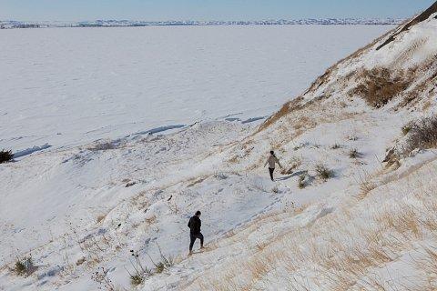 Partners Joseph White Eyes, left, and Danny Grassrope walk toward the Missouri River. Grassrope, who is Kul Wicasa Lakota, grew up in Lower Brule. White Eyes, who is Blackfoot Lakota, is from South Dakota's Cheyenne River Reservation. <br>Lower Brule, South Dakota, Febraury 2019.