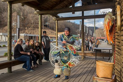 """Chad Feather, 34, works in downtown Cherokee where he dances pow wow style – a blend of many nations and traditions – for tourists. Referred to as """"Chiefing,"""" dancing and posing for pictures with tourists has historically been on the frontline of educating tourists about Cherokee culture. """"Chiefing,"""" which dates back to the 1930s, has become controversial on the boundary in recent years.  <br>Cherokee, North Carolina, January 2019."""