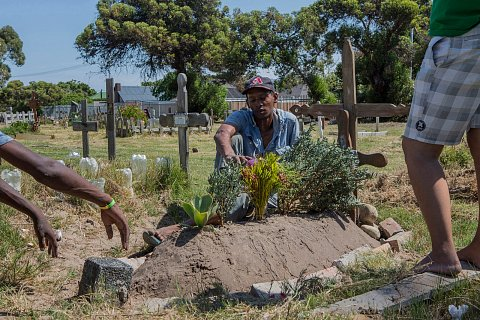 Friends and family visit the grave of Ashwin Pietersen who was murdered outside his home in Manenberg by a rival gang member. <br>Plumsted, December 2018.