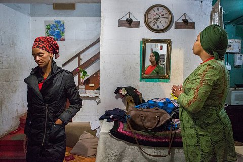 Naomi Lottering, left, and her sister, Debby, pray together inside Debby's home before leaving for a Saturday night church service. <br>Manenberg, April 2017.