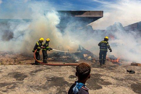 A fire is extinguished behind the petrol station. <br>Manenberg, December 2019.