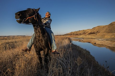 Mahto In The Woods, 19, rides a horse on the Cheyenne River Reservation in South Dakota. In The Woods does not trust the U.S. government or the Covid-19 vaccine and has chosen not to get vaccinated. When he was 17 years old, he was in a serious car accident that left him unable to walk and half his face paralyzed. He began riding horses to heal and is now an accomplished horseman and racer. He rides on his family's land along the Moreau River, the same land on which Crazy Horse and Sitting Bull used to camp. March 11, 2021.