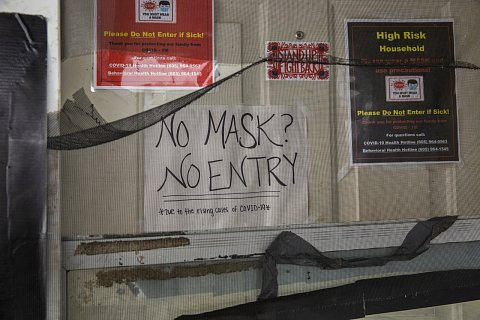 Signs on the door of the Edwards's home in Eagle Butte instruct visitors to wear a mask and not to enter if sick. Several family members, spanning three generations, live inside the house, including elders Joyce Edwards, 64, and her husband, Calvin Edwards, 62. October 30, 2020.